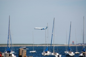 Jetliner approaching Logan Airport as sailboats are moored in harbor waters in Boston, Mass.