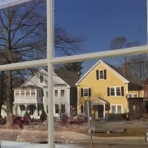 Houses reflected in window of Brick Store Building, Old Center, North Andover, Mass.