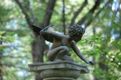 bronze young crouching Cupid at Tower Hill Botanic Garden