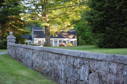 stone wall and cape style house