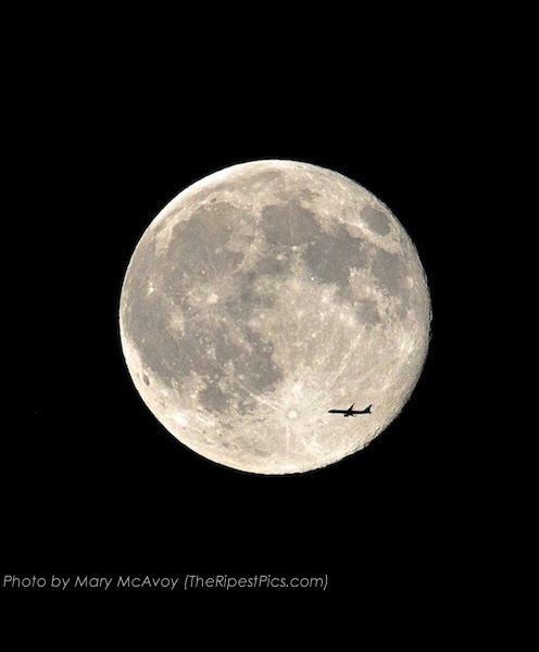 supermoon with jetliner passing by